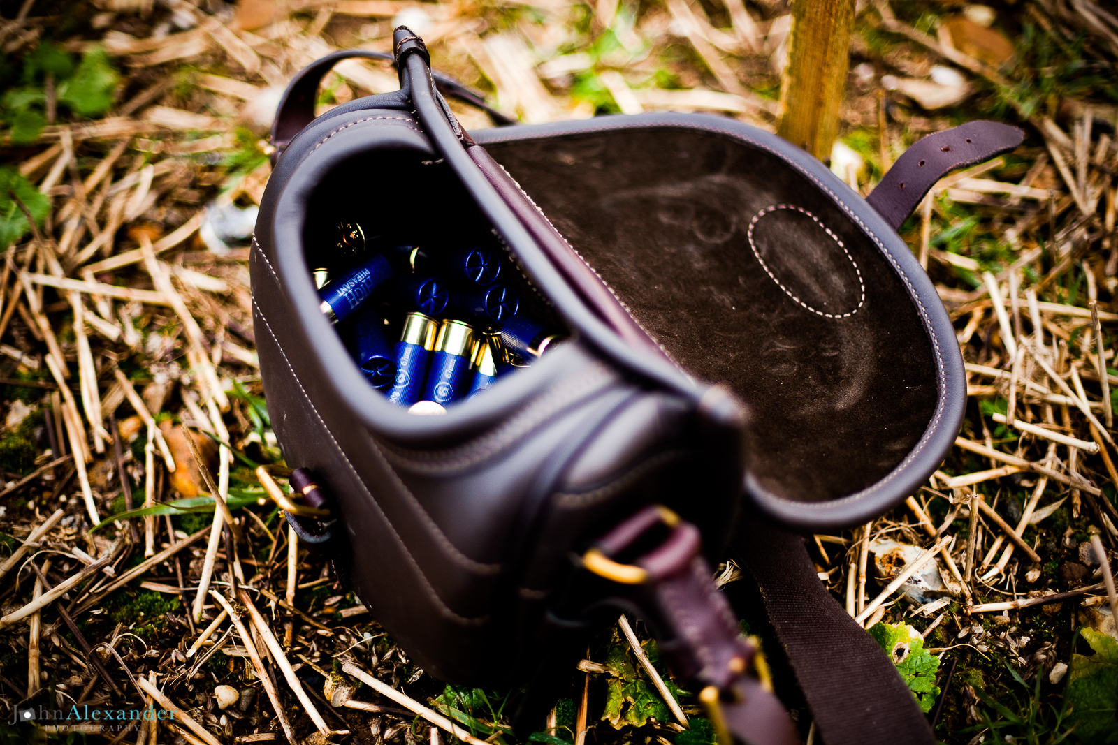 Brown leather shotgun cartridge loader bag. Filled with blue cartridges, on the ground
