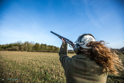Young Lady Gun shooting pheasant in blue sky