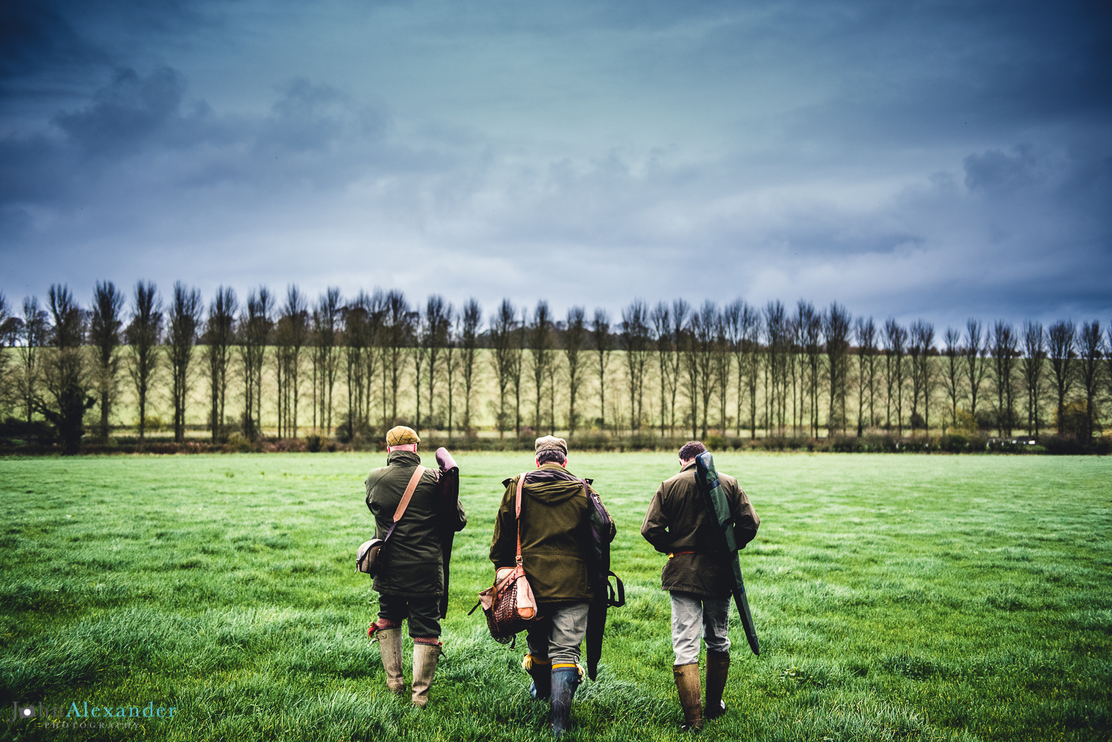 3 guns walking through a field on a pheasant shoot
