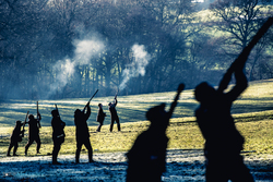silhouette of line of guns shooting pheasants on driven game shoot