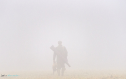 gun walking in the mist with shot pheasant