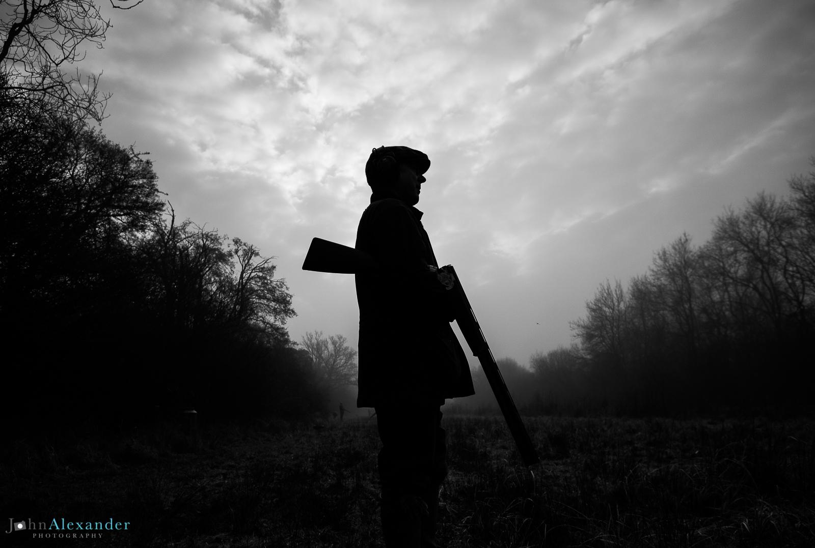 silhouette of gun with shotgun cocked under arm