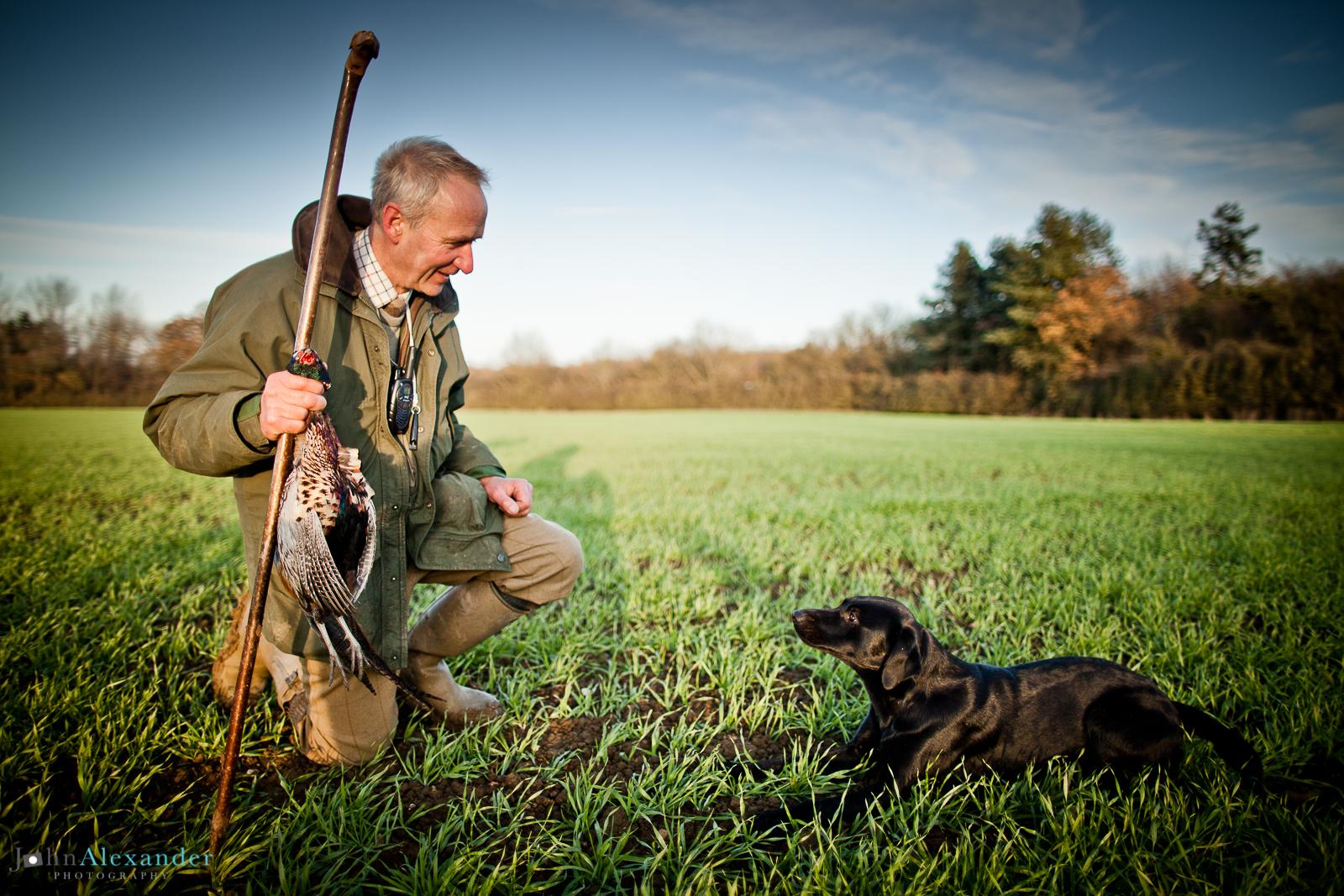 gun looking at black labrador gun dog with pheasant in hand