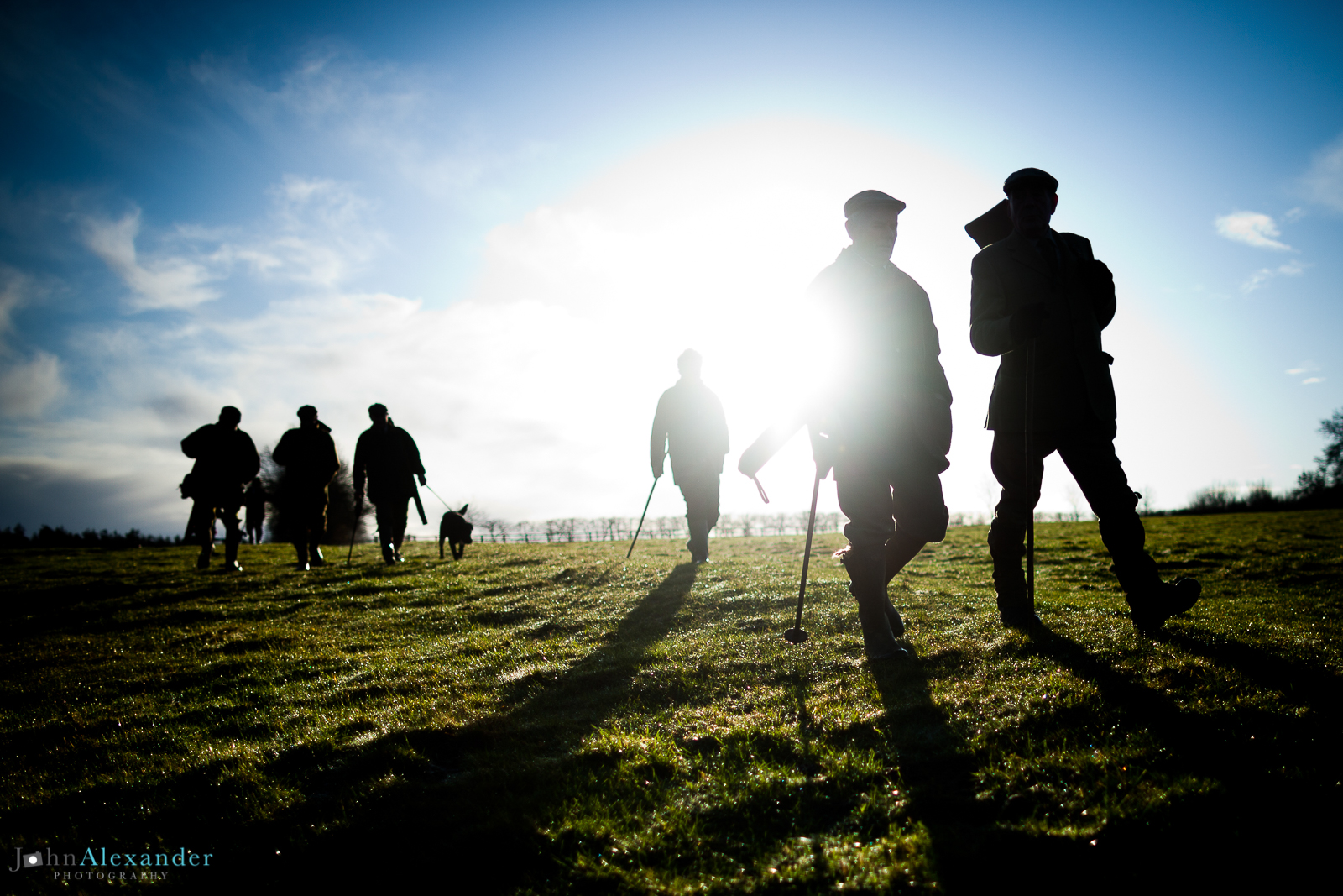 silhouettes of guns walking through a field