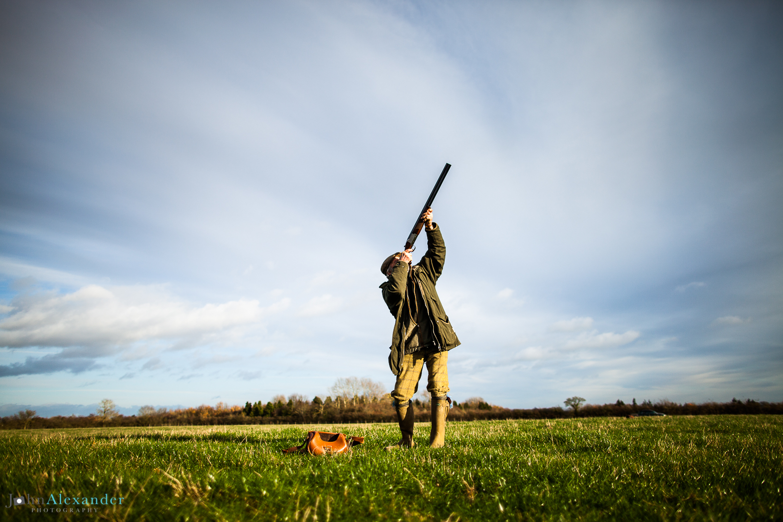 gun shooting high pheasant from low angle