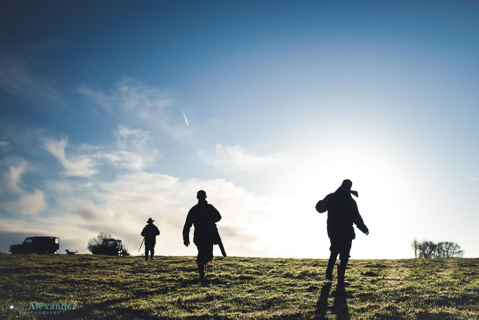 silhouettes of guns walking through field