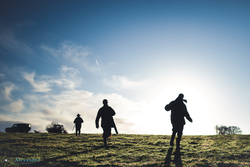 silhouettes of guns walking through field