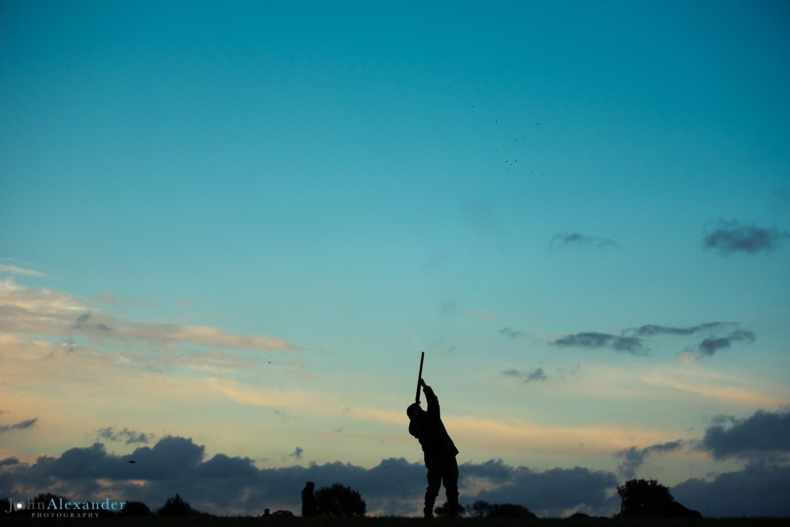 Silhouette of a gun aiming high into a blue sky