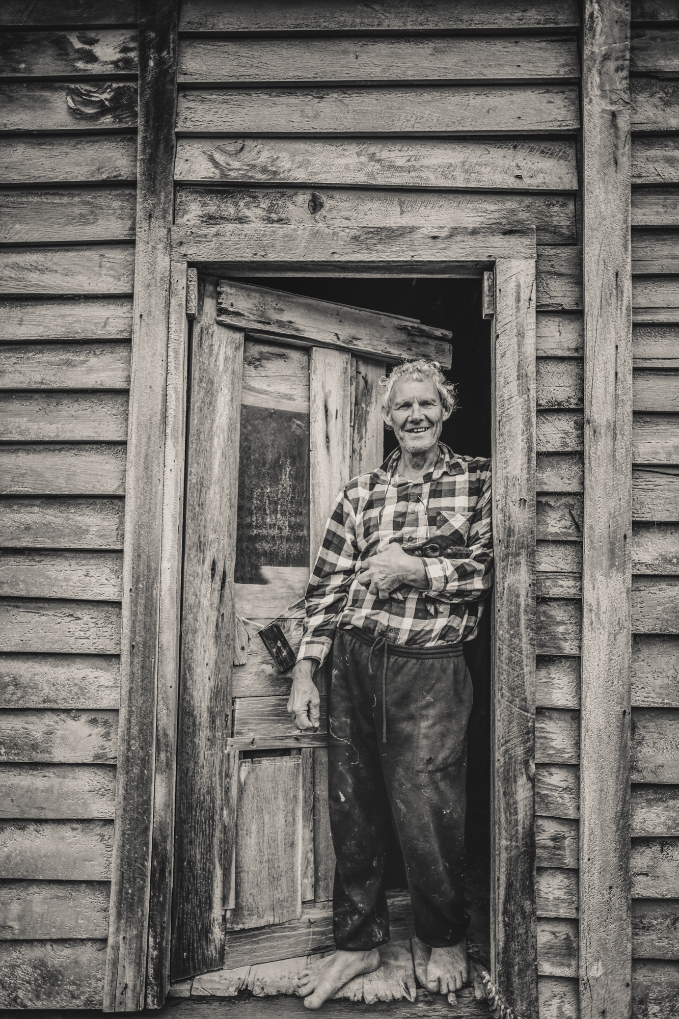 Portrait of a man standing outside his front door