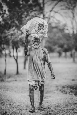 Sri Lankan Man carrying a sack in black and white