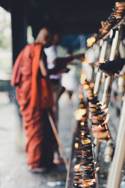Bhuddist Monk lighting candles