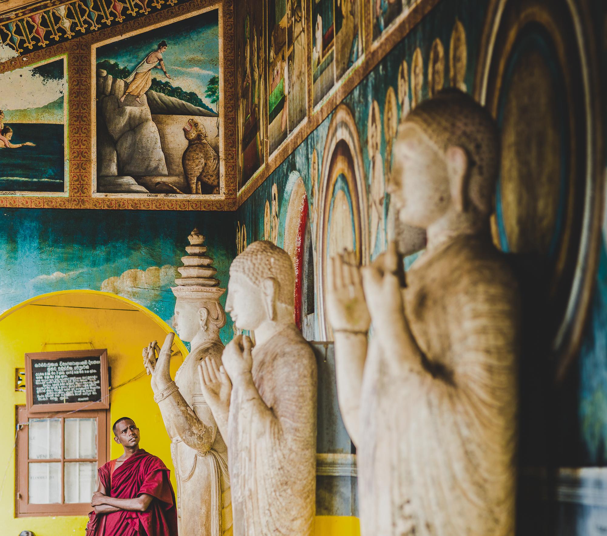Monk looking at statues of Bhudda