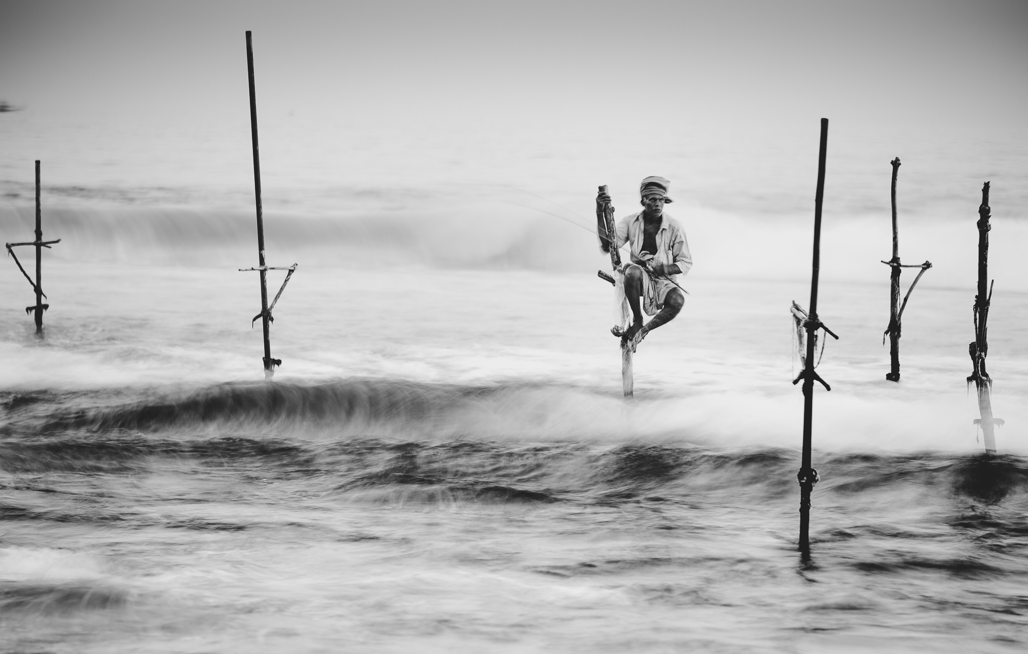Black and white image of stilt fishermen